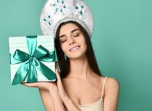 Portrait of a pretty smiling gir in traditional russian cap kokoshnik holding gift box royalty free stock images