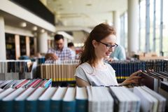 Portrait of a pretty smiling girl reading book in library. Portrait of a pretty smiling girl reading book indoors in library Stock Images