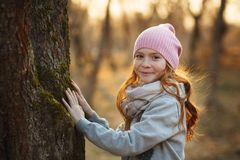Portrait of a pretty smiling girl with red hair and freckles near a tree. Spring or autumn park or forest. Sun rays. Concept of royalty free stock photo
