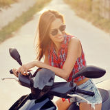 Portrait of pretty smiling girl on scooter Royalty Free Stock Photos