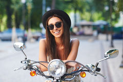 Portrait of pretty smiling girl on scooter Stock Image