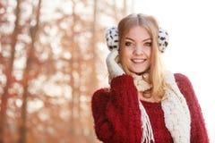 Portrait of pretty smiling woman in earmuffs. Stock Photo