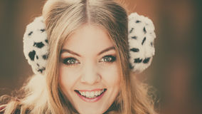 Portrait of pretty smiling woman in fur earmuffs. Royalty Free Stock Photos