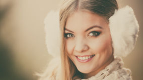Portrait of pretty smiling woman in fur earmuffs. Royalty Free Stock Image