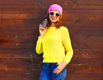 Portrait pretty smiling woman holding coffee cup in colorful clothes over wooden background wearing pink hat. Yellow sweater Royalty Free Stock Photo