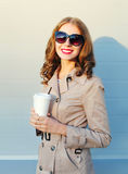 Portrait pretty smiling woman holds coffee cup wearing coat black sunglasses in city evening. Portrait pretty smiling woman holds coffee cup wearing a coat black Stock Photography