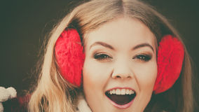 Portrait of pretty smiling woman in red earmuffs. Stock Images