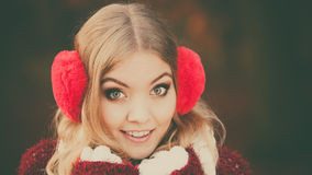 Portrait of pretty smiling woman in red earmuffs. Royalty Free Stock Photos