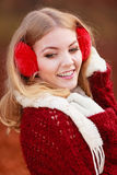 Portrait of pretty smiling woman in red earmuffs. Royalty Free Stock Image
