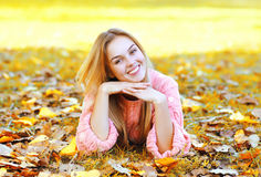 Portrait pretty smiling woman resting lying on leaves in autumn Royalty Free Stock Photography