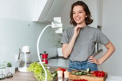 Portrait of a pretty smiling woman watching movie. On mobile phone on a long arm holder while cooking at the kitchen Stock Photo
