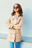 Portrait pretty smiling woman wearing a coat and black sunglasses stands over grey. Background Royalty Free Stock Images
