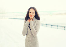 Portrait pretty smiling woman wearing a knitted sweater outdoors in winter. Day Stock Photo
