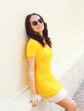 Portrait of pretty smiling woman wearing a yellow dress. And sunglasses in the city Stock Photo