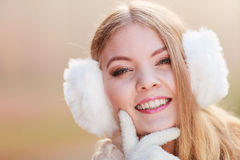 Portrait of pretty smiling woman in white earmuffs Royalty Free Stock Photo