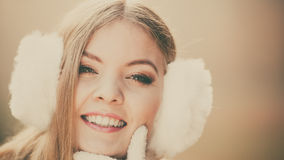 Portrait of pretty smiling woman in white earmuffs Royalty Free Stock Image