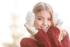 Portrait of pretty smiling woman in white earmuffs. Stock Photos
