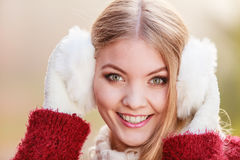 Portrait of pretty smiling woman in white earmuffs. Royalty Free Stock Images