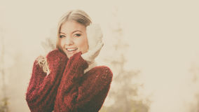 Portrait of pretty smiling woman in white earmuffs. Royalty Free Stock Photography