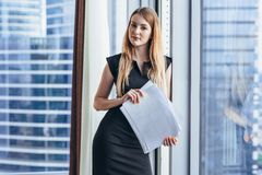 Portrait of pretty smiling young woman holding papers standing at window with cityscape view royalty free stock images