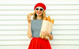 Portrait pretty smiling young woman wearing red beret holding cr. Oissant, paper bag with long white bread baguette on white wall background royalty free stock photos