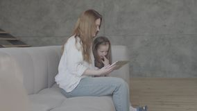 Portrait pretty smilling young mother and her adorable cute little daughter are using a tablet and smiling, sitting on. Beautiful young mother and her cute stock footage