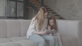 Portrait pretty smilling young mother and her cute little daughter are using a tablet and smiling, sitting on sofa in. Beautiful young mother and her cute little stock video footage