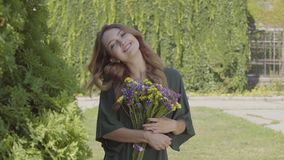 Portrait of pretty smilling young woman holding bouquet of wild flowers looking at camera while standing outdoors stock video footage