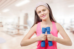Portrait of pretty sporty girl holding weights Stock Photos