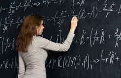 Portrait of a pretty student doing maths on a blackboard Royalty Free Stock Images