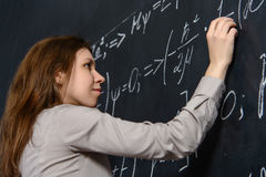 Portrait of a pretty student doing maths on a blackboard Stock Photos
