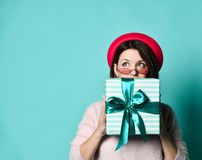 Portrait of a pretty surprised girl in felt hat cap holding gift box and hiding behind him, looking up royalty free stock image