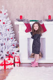 Portrait of pretty sweet little girl near a fireplace in Christmas. Portrait of pretty little girl near a fireplace in Christmas royalty free stock images
