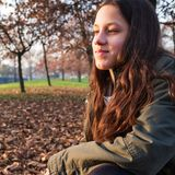 Smiling young teenage girl sitting in autumn park stock photos