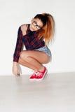 Portrait of a pretty teenage girl crouching Stock Image