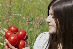 Portrait of a pretty teenage girl holding tomatoes Royalty Free Stock Photography