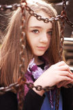 Portrait of a pretty teenage girl looking through some chains. At a play park royalty free stock images