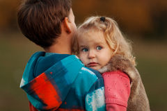 Portrait of pretty thoughtful sister and brother in autumn park. Outdoor Stock Photos