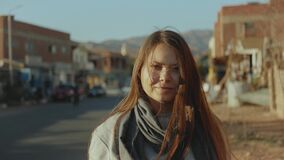 Portrait of pretty tourist woman standing on the street at city Dahab background, Egypt, Sinai, slow motion, 4k