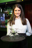 Portrait of pretty waitress holding a tray with wine glasses Stock Photography