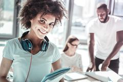 Portrait of pretty woman that being ready to work. Have a look. Cheerful dark-skinned girl keeping smile on her face and having headphones on her face while stock photos