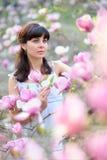 Portrait pretty woman in a blossoming spring magnolia garden Stock Photos
