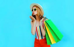 Portrait pretty woman blowing red lips sends air kiss with shopping bags in colorful t-shirt, summer round hat on blue. Background stock image