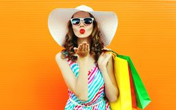 Portrait pretty woman blowing red lips sends sweet air kiss with shopping bags wearing colorful striped dress, summer straw hat royalty free stock images
