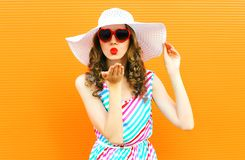 Portrait pretty woman blowing red lips sends sweet air kiss wearing summer straw hat, colorful striped dress on orange wall stock photo