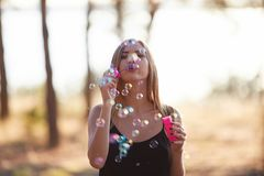 Portrait of pretty woman with bubbles, traveler relaxing in forest. Royalty Free Stock Image