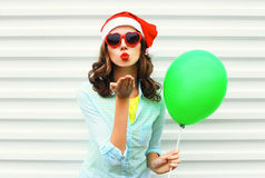Portrait pretty woman in christmas red santa hat, with air balloon, heart sunglasses sends air kiss on white background Royalty Free Stock Image