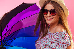 Portrait of a pretty woman with clororful umbrella wearing sunglasses. On pink background Royalty Free Stock Photo