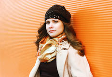 Portrait pretty woman in coat and hat against colorful wall Stock Photo