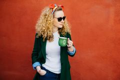 Portrait of pretty woman with curly hair wearing headband, stylish sunglasses and green jacket holding green cup of tea in one han royalty free stock photo